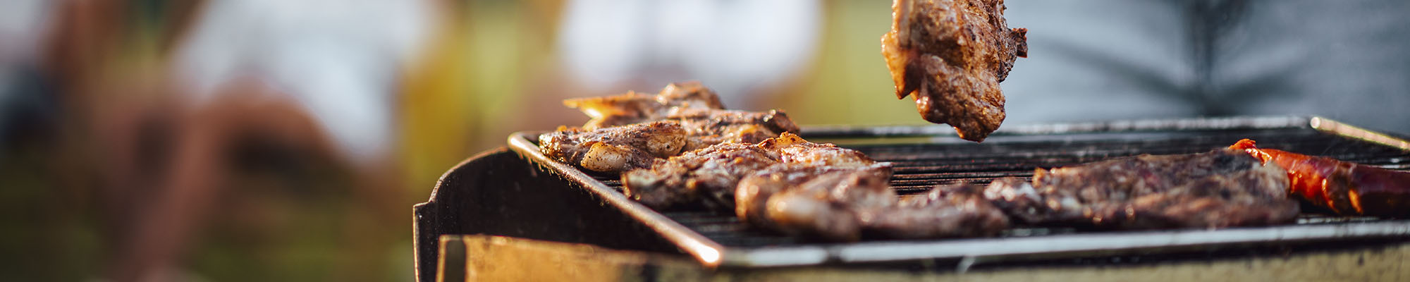 En grillbild ute i naturen. Kött ligger på en grill.